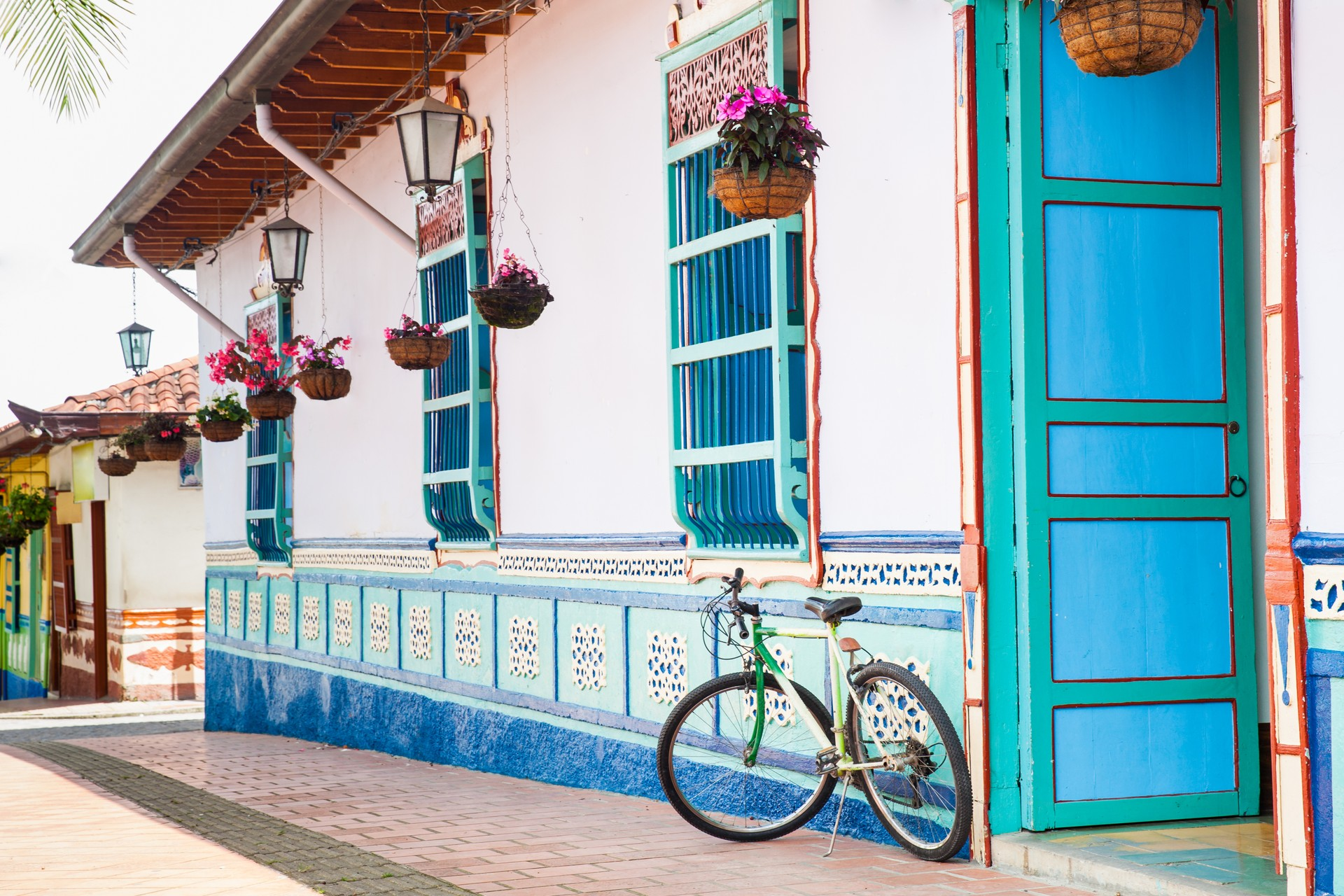 A bike leans against a colourful house in Guatapé, Colombia