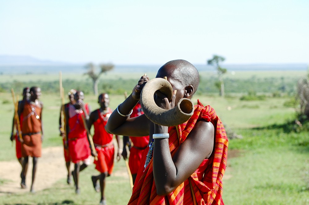A Maasai man blows on a horn