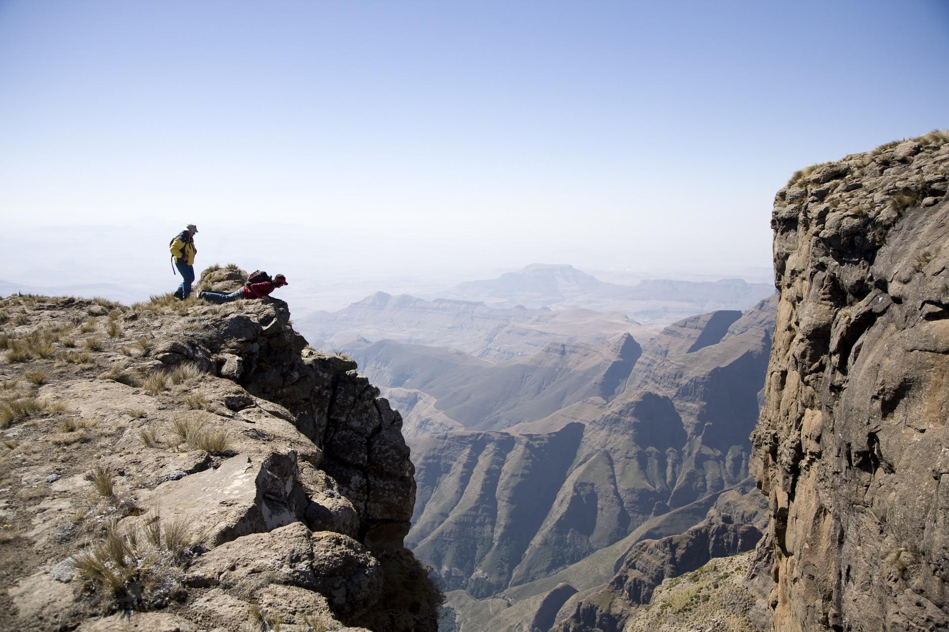 Hikers peering over cliff in Drakensberg Amphitheatre