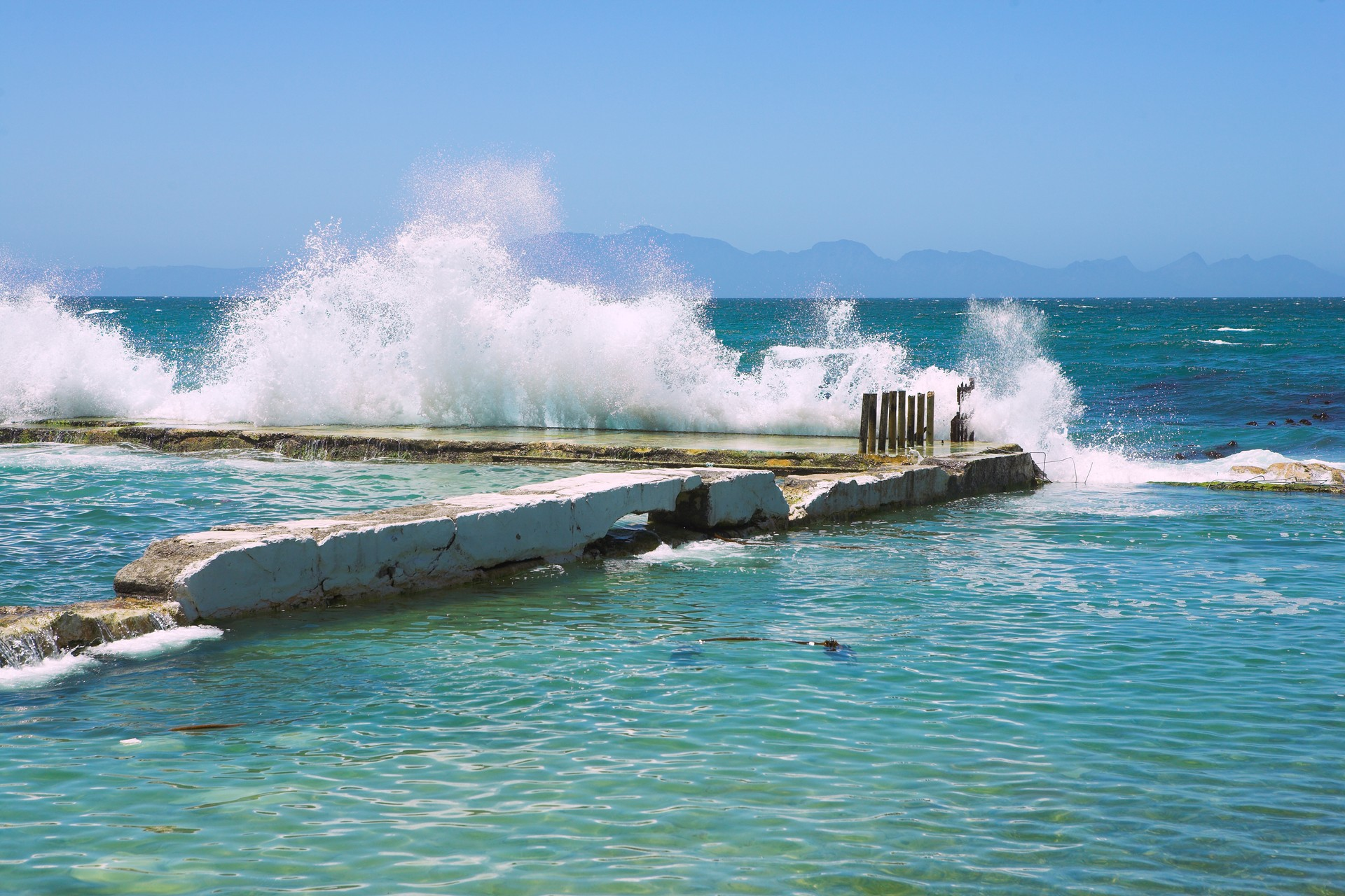 Waves breaking against the wall of a tidal pool in Kalk Bay
