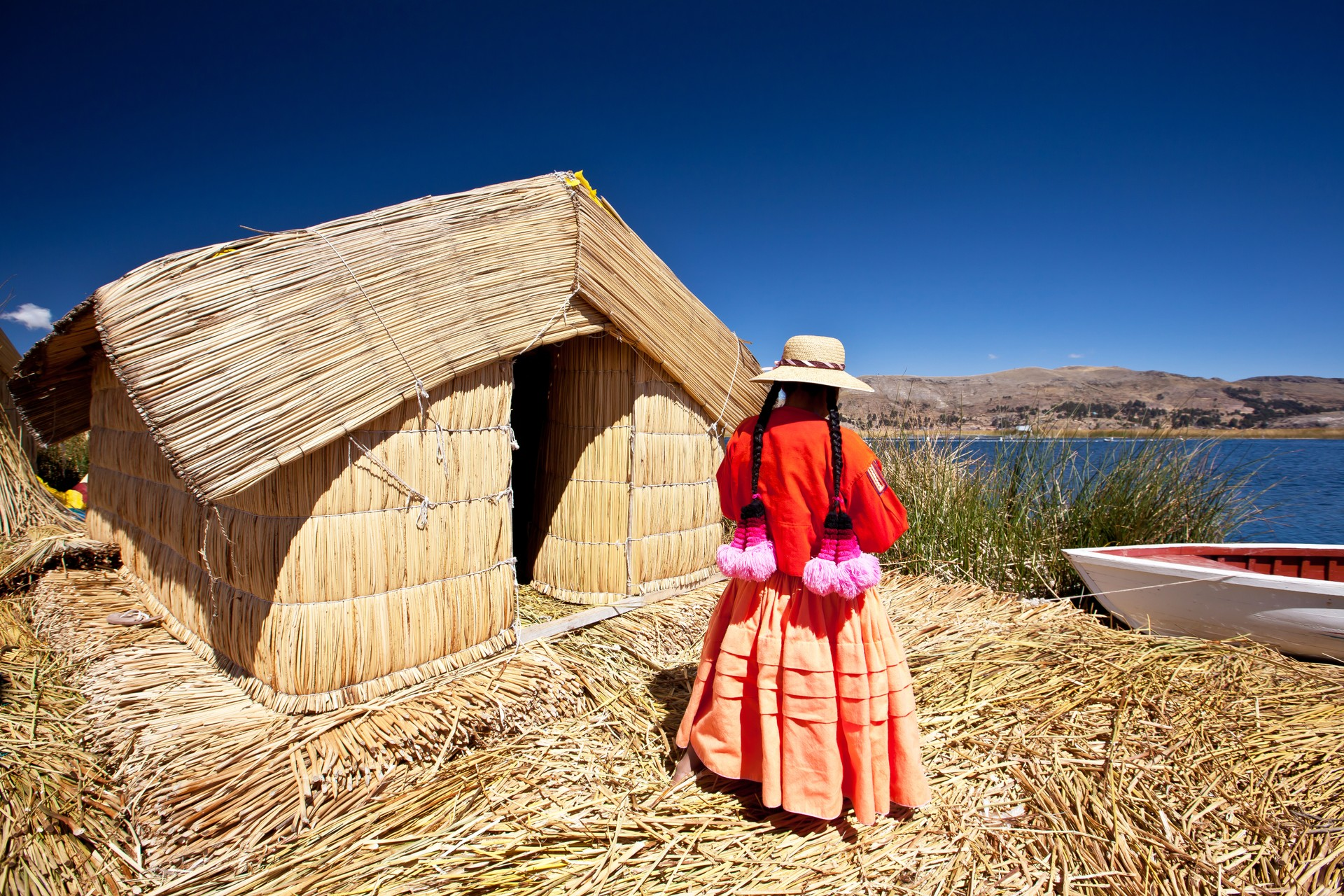 An indigenous woman stands outside of the house she has built from reeds in Puno, Peru