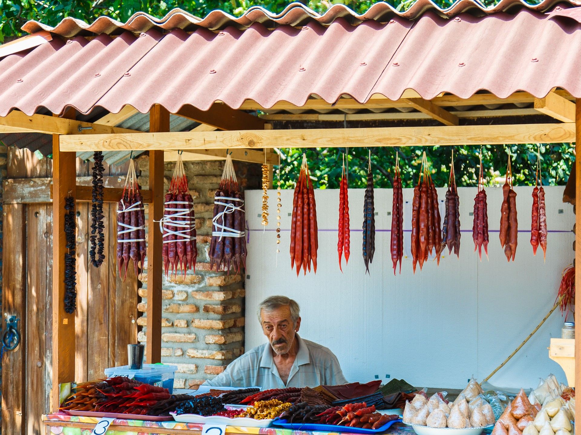 A man selling churchkhela and chestnuts in Tbilisi