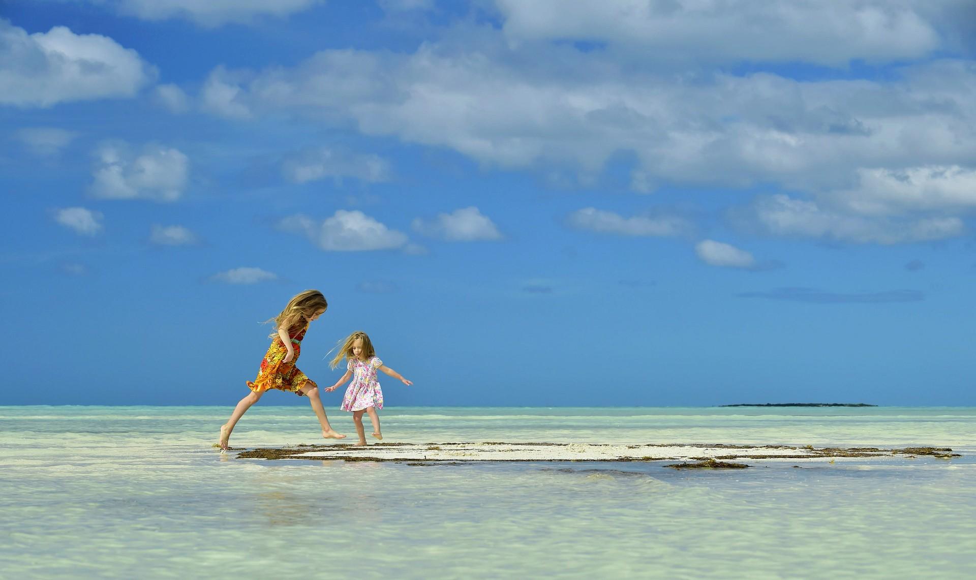 Two girls play on a sandbank in Caya Coco in Cuba