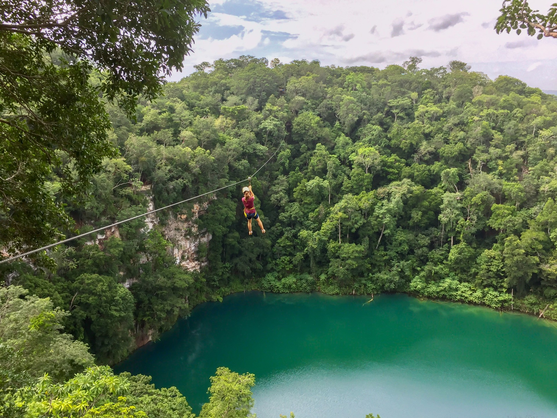 A girl zipwires across a cenote in the rainforest in Mexico