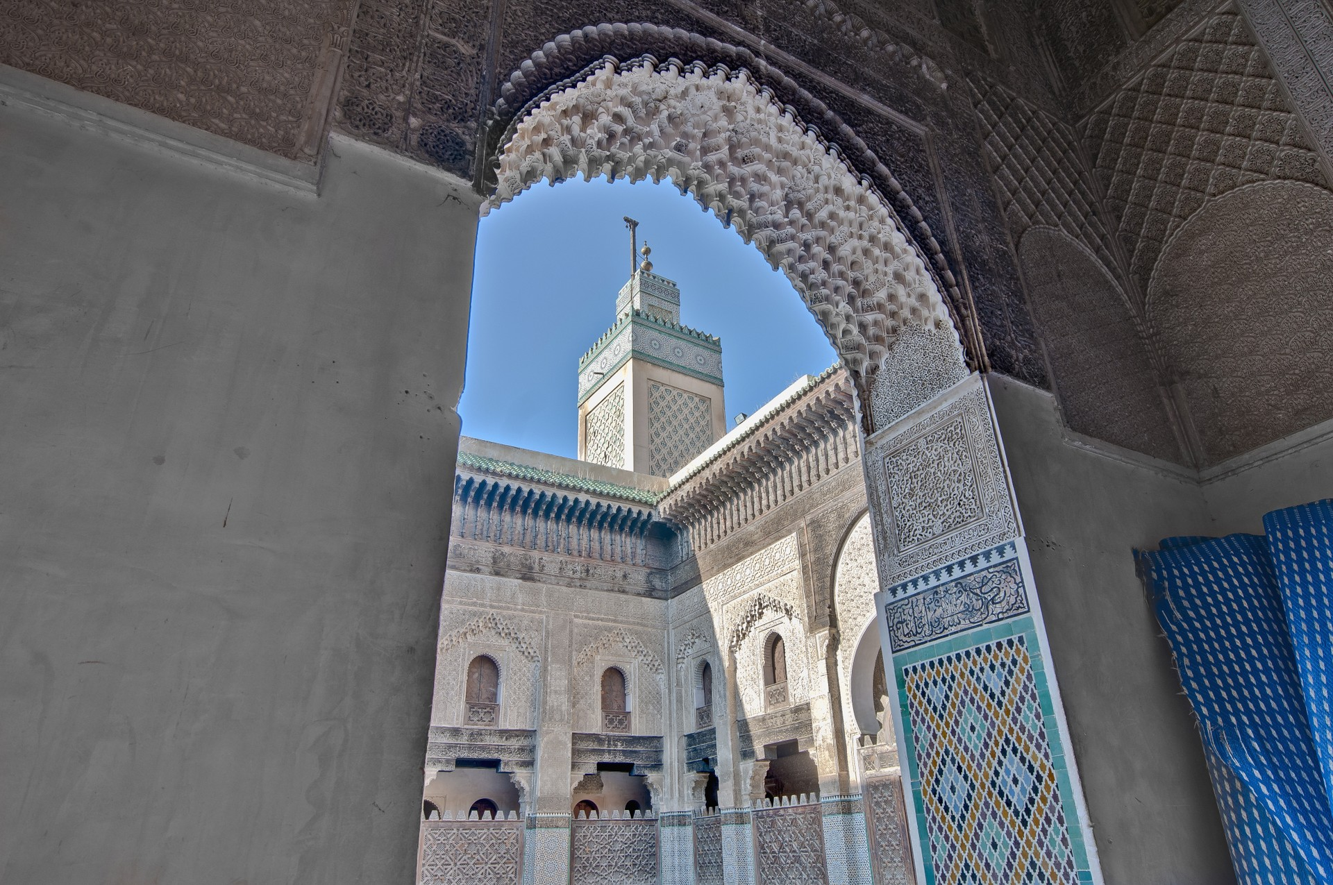 The intricate walls and blue minaret of the Medersa Bou Inania in Fes, Morocco