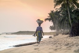 Lady walking along beach at sunset, Senegal