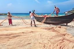 Fishermen tending nets on the beach