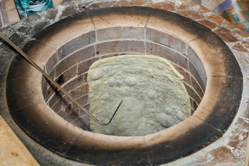 Lavash bread cooking in a tonir