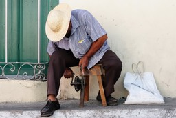 A Cuban man sharpens a knife in the street