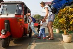 Mother helps children into tuk tuk